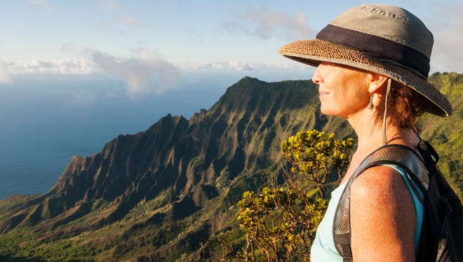 A woman looks out at the landscape at Kalalau.