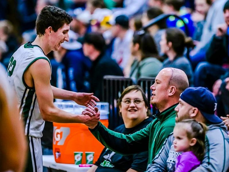 Kurtis Kodet, left, of Williamston congratulates Williamston head coach Jason Bauer late in the 4th quarter of their Class B regional final win over Stockbridge Wednesday at Eaton Rapids High. Bauer was sidelined by brain tumors.