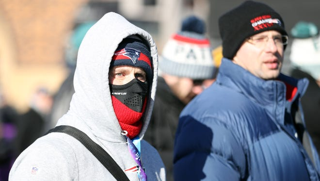 Fans are bundled up as they wait outside of U.S. Bank Stadium.