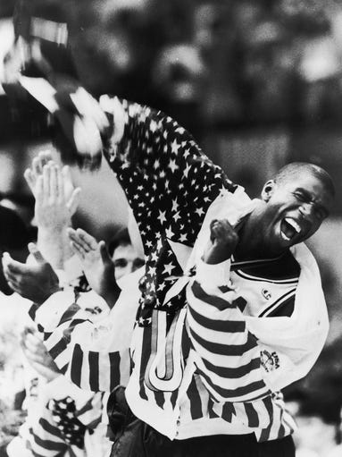 Magic Johnson of Lansing screams as he lifts the American