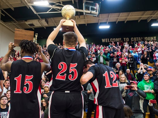 From left, Rutland's #15 Tyrell Johnson, #25 Nathaniel Kingsley, and #12 Kyle Cassarino celebrate with fans after winning the Vermont state boys high school championship at Patrick Gymnasium in Burlington on Monday night, March 13, 2017. Rutland won for the first time in 50 years, 43-37, over CVU after a tie forced the game into overtime.