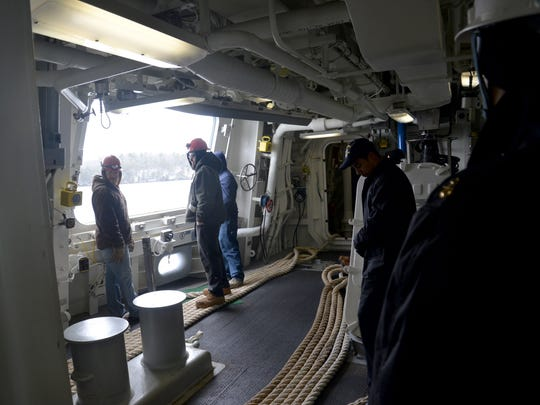 Shipbuilders from Bath Iron Works stand by to handle