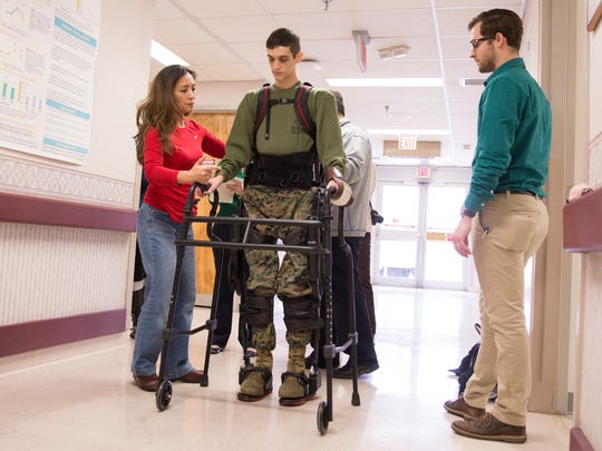 Physical therapists guide Cpl. Josh Burch as he walks
