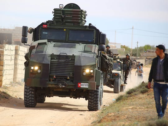 Tunisian soldiers ride armored vehicles as they search