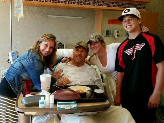 John Sain poses for a photo with his family while recovering