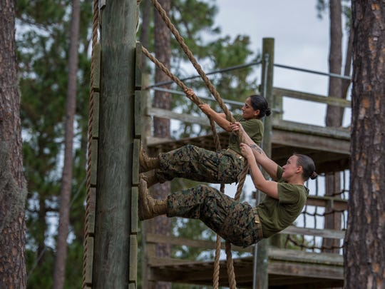 Female Marine recruits complete an obstacle course