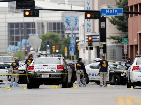 Investigators work in the area of downtown Dallas that