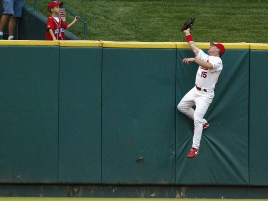 Jim Edmonds of the St. Louis Cardinals robs Adam Dunn of the Cincinnati Reds of a home run in a 2004 game at Busch Stadium. (Photo by Elsa/Getty Images)