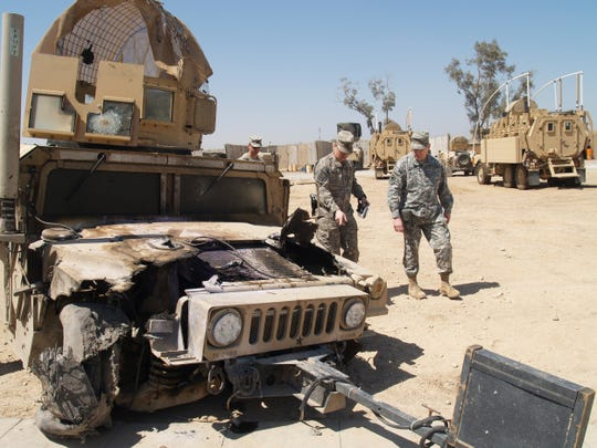 U.S. soldiers inspect a humvee damaged in 2009 by an