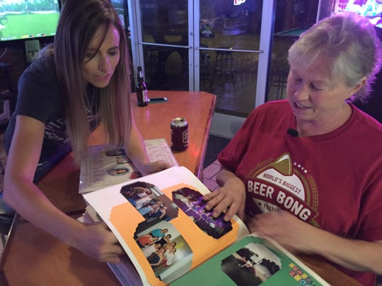 Sara Erlandson looks through scrapbooks with her mother,
