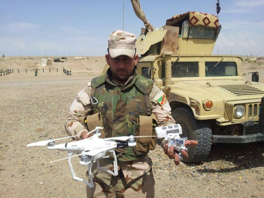 Iraqi Sgt. Hussain Musa Kathum displays an ISIS drone