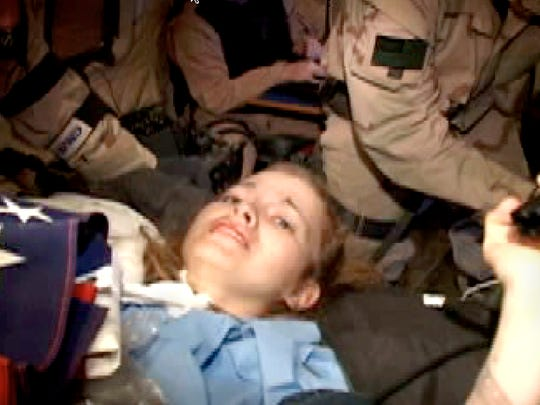 Pfc. Jessica Lynch is loaded into a military helicopter