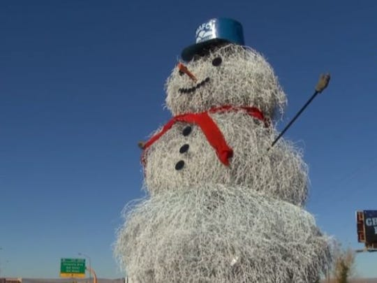 A snowman made of tumbleweed wears a trucker's hat.
