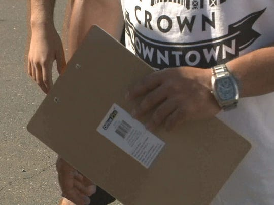 Signature gatherers ask people to sign petition.