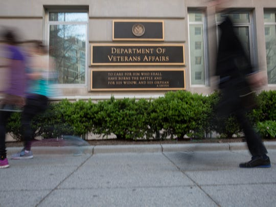 People walk by the Department of Veteran Affairs in