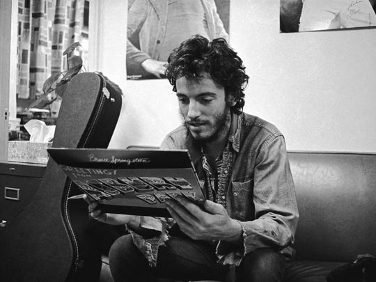 "Bruce Springsteen in 1973 with a copy of ""Greetings from Asbury Park, N.J."""