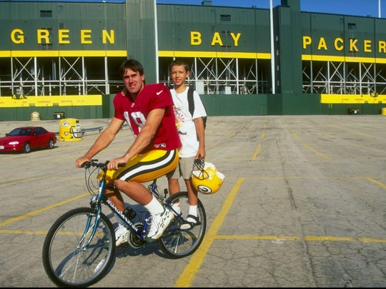 Quarterback Doug Pederson #18 of the Green Bay Packers gives a fan a ride on a bike during the Packers Training Camp at Lambeau Field in Green Bay, Wisconsin.