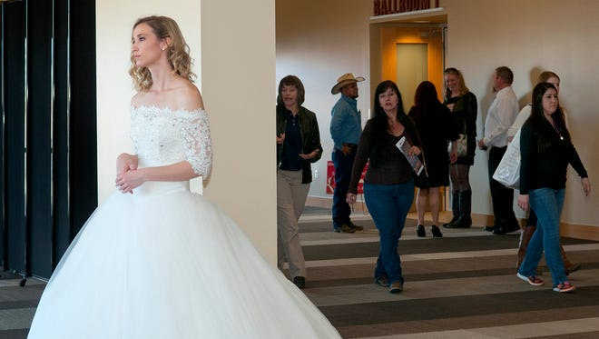 Sarah Kidd, modeling a bridal dress from Renee's Bridal, meets bridal show goers at the entrance of the Las Cruces Convention Center Sunday afternoon. 