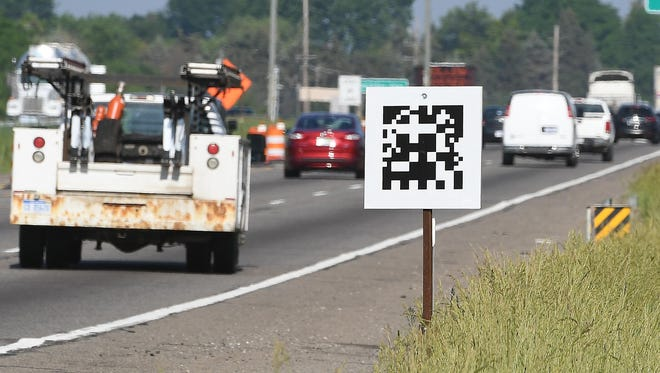 QR-like codes on I-75 road signs in Oakland County communicate information about a construction zone to connected vehicles.
