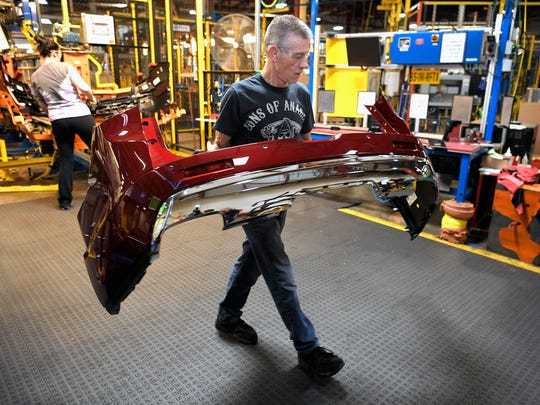 Bruce Muenstermann carries a car bumper at the General Motors plant in Spring Hill, which produces the Cadillac XT5 and the GMC Acadia.