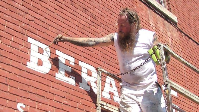 Sign painter Gibbs Connors, of Philadelphia, works on a new mural on the outside of the Howell Liberatore & Associates building in Elmira.