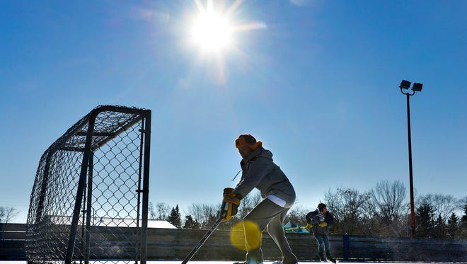 University of Minnesota junior Andrew Abraham, 20, gets in a little hockey practice with two friends including Carson Muehlbauer, right,  and Samuel Hastings on Tuesday on the hockey rink at Raymond Park. The three are Sauk Rapids-Rice High School graduates, all home on winter break.