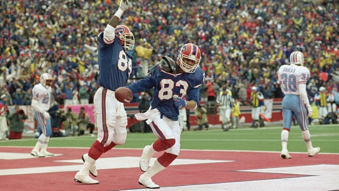 Buffalo Bills wide receiver Andre Reed (83) and teammate Keith McKeller celebrate Reed's third touchdown during the fourth quarter against the Houston Oilers, Jan. 3, 1993 at Rich Stadium in Orchard Park, N.Y.  The Bills staged the biggest comeback in NFL history to beat the Oilers 41-38 in overtime.