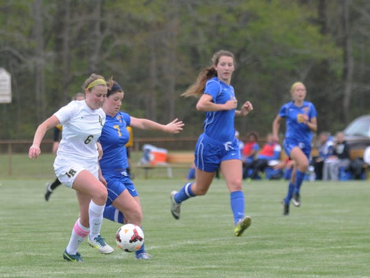 Indian River's Sarah Buchler fights off a Caesar Rodney defender to score a goal. Buchler is a captain and her move from defense to midfield has helped the Indians this season.