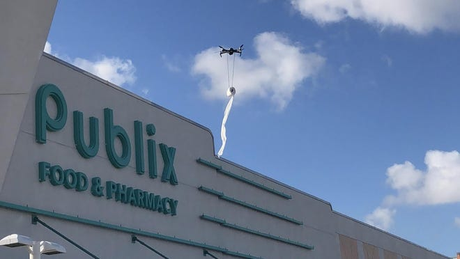 The toilet paper drone launched by Chad Rondeau rises over Publix in Lake Worth Beach Wednesday.