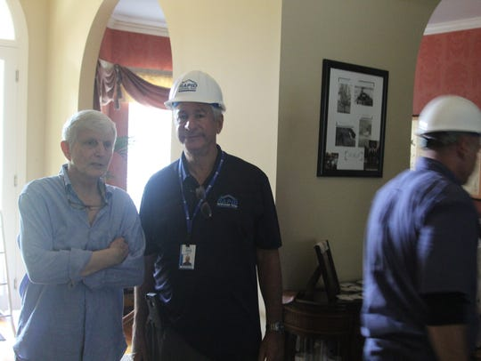 Dr. Myrle Grate, left, discusses the damage to his