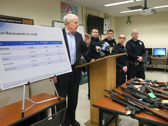 Milwaukee Mayor Tom Barrett discusses seized firearms Sunday at a news conference at the Milwaukee Police Department's District 7 station. He used a chart to compare the number of guns taken off the street to other cities by population. Also pictured (from left) are officers Chad Boyack, Anthony Milone, Rebecca Rodriguez and Daniel Tierney.