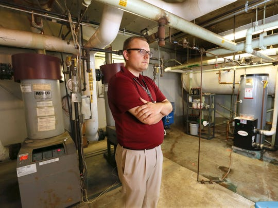 Jonathan Mitchell, director of finance and operations at the St. Francis School District, stands in front of boiler heating units at Deer Creek Intermediate School.
