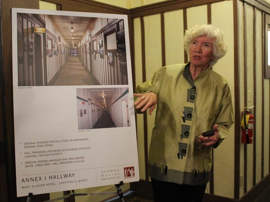 Nan Anderson, principal architect, stands beside a poster depicting the changes to the Many Glacier Hotel's hallways.