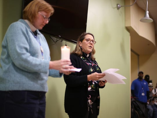 Grace Mission Pastors Amanda Nickles, right, and Jenni Liem read through a list of dozens of names of people who had passed through the doors of the Kearney Center, and died over the last year, during a National Homeless Persons' Memorial Day ceremony last year.