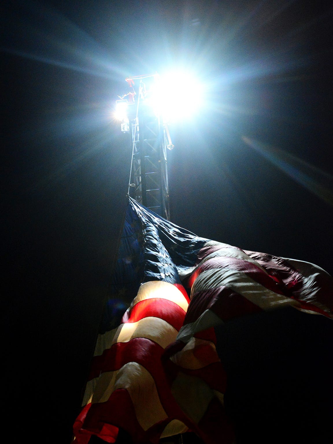 """An American flag is raised at West Jackson Baptist Church as law enforcement officers from across Tennessee and other areas around the nation gathered to honor fallen Madison County Sheriff's Deputy Rosemary Vela in a """"Sea of Blue"""" on Thursday evening."""