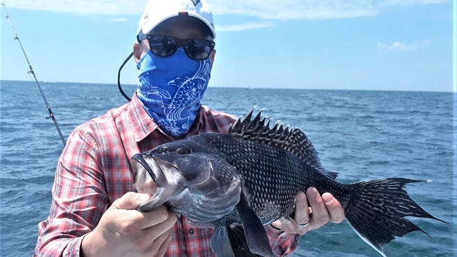 Chris Jones of North Kingstown with a 22-inch black sea bass he caught Sunday at Elbow Ledge.