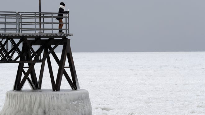Michele King, 26, looks out over frozen Lake Erie, Wednesday, Jan. 3, 2018, in Cleveland. Dangerously cold temperatures have gripped wide swaths of the U.S. from Texas to New England.