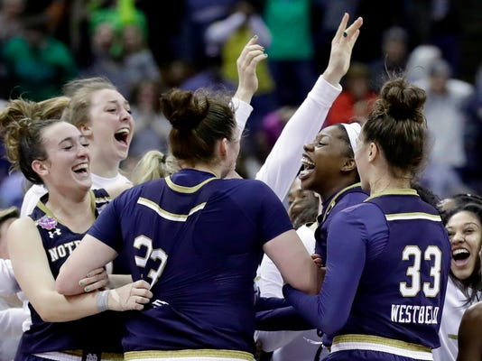 Notre Dame's Arike Ogunbowale, second from right, is congratulated by teammates after making the game-winning basket to defeat Connecticut in overtime in the semifinals of the women's NCAA Final Four college basketball tournament, Friday, March 30, 2018, in Columbus, Ohio. Notre Dame won 91-89. (AP Photo/Ron Schwane)