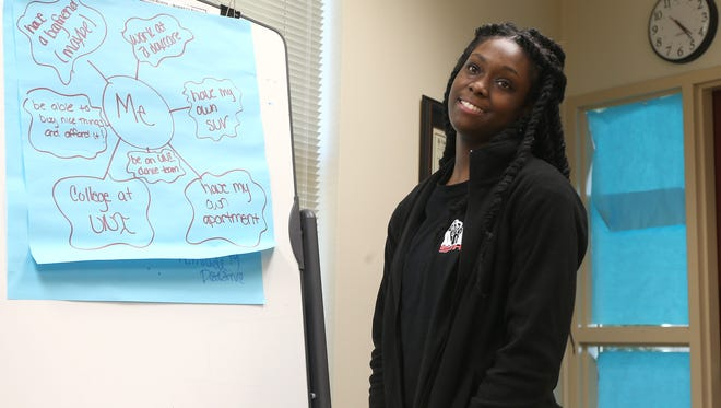 Asia Nash, 18, of Waterloo writes her goals on a sheet of paper during a group meeting in October 2014 at Allen College in Waterloo. The group — Sistas Informing, Healing, Living and Empowering — aims to help teens prevent pregnancies and sexually transmitted diseases.