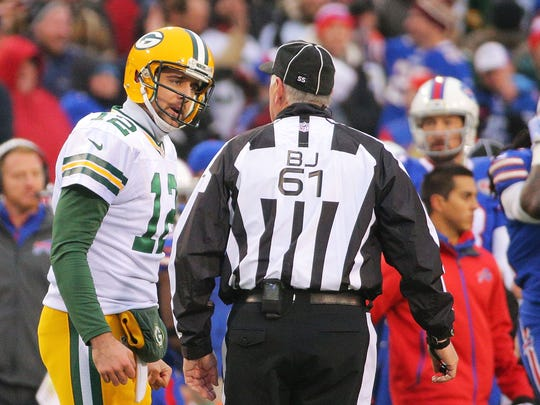 Aaron Rodgers #12 of the Green Bay Packers talks to the back judge Keith Ferguson #61 during the second half against the Buffalo Bills at Ralph Wilson Stadium on December 14, 2014 in Orchard Park, New York.