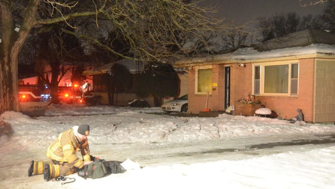 Firefighters gather equipment after fighting a fire Christmas morning in Battle Creek.