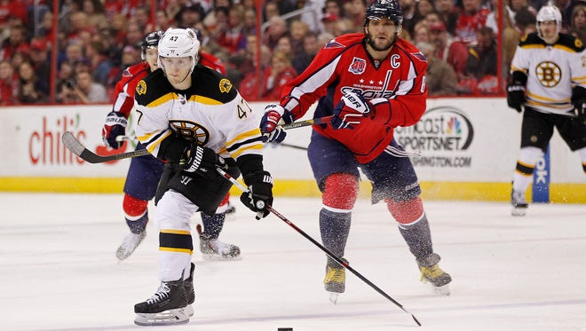 Boston Bruins defenseman Torey Krug (47) skates with the puck as Washington Capitals left wing Alex Ovechkin (8) defends in the third period at Verizon Center.
