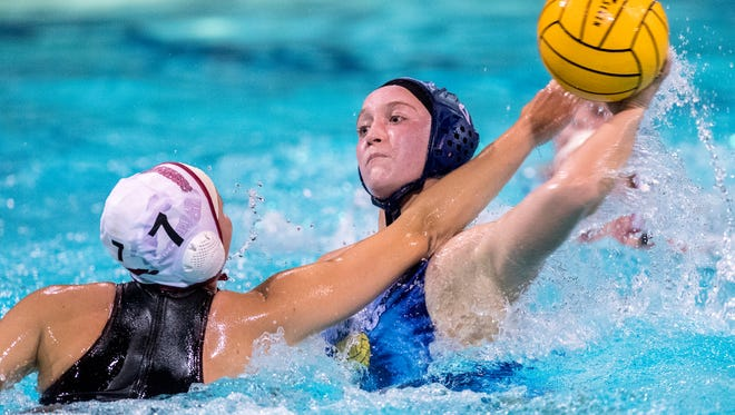 Redwood's Skylar Ford shoots under pressure from Carondelet's  Gigi Baldacci in a CIF NorCal regional first-round state playoff girls water polo game on Tuesday, November 14, 2017.
