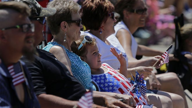 Jazmyn Cloutier finds a comfortable spot with Nancy Foegen to wave as the 67th annual Appleton Flag Day Parade passes by in Appleton.
