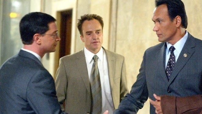 Jimmy Smits, right, shakes hands with Joshua Malina as Bradley Whitford, center, watches.