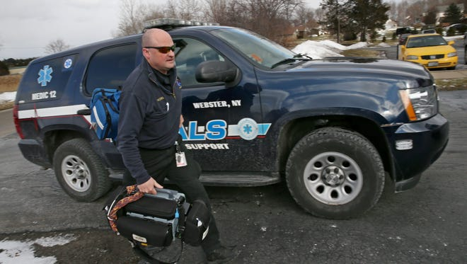 Rick Yeckel, paramedic with North East Quadrant Advanced Life Support, races to a call in Webster, with his Lifepak in hand.