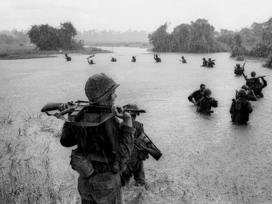 In this Sept. 25, 1965 file photo, paratroopers of the U.S. 2nd Battalion, 173rd Airborne Brigade hold their automatic weapons above water as they cross a river in the rain during a search for Viet Cong positions in the jungle area of Ben Cat, South Vietnam.