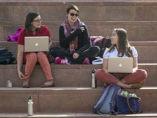 ASU graduate students Haley Honeman (from left), Ashley Laverty and Rivka Rocchio study in Tempe. Upon graduation, Honeman and Laverty believe they will have more than $20,000 in student loans, while Rocchio is trying to stay debt-free. The for-profit col