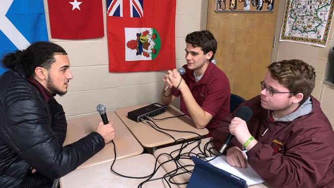 Cardinal Spellman High students Anthony Nardelli, right, and Thomas Sullivan, middle, interview Cardinals basketball and football star Craig Faria for their podcast. Contributed photo/Daniel Higgins