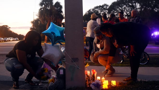 Oveda Taylor (from left), Soirnilia Pierre and Megan Barron place flowers and light candles at Cortez and Sunrise boulevards in Fort Pierce on Tuesday, Dec. 26, 2017, in memory of Issac Santillan, 9, who died in a car crash early Christmas morning. All three women work for Sunrise Preschool, where Santillan attended after-school programs.